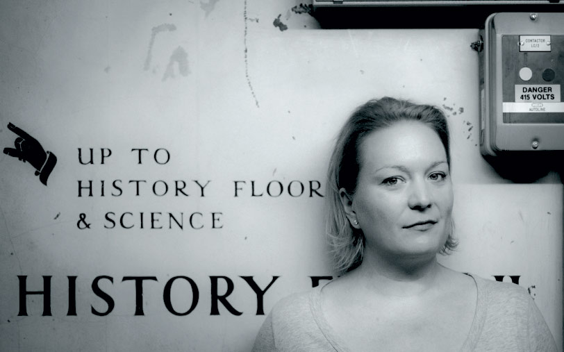 Writer Lucy Inglis in front of a sign in a bookshop pointing to History.